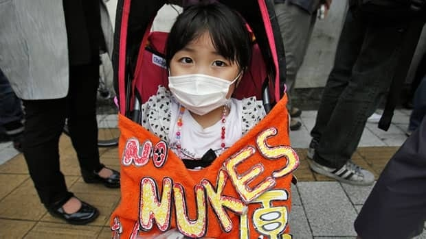 Kaede Tanaka, 3, sits in her buggy with a Geiger counter placed on her lap, during an anti-nuclear protest in front of the Japanese prime minister's official residence in Tokyo.