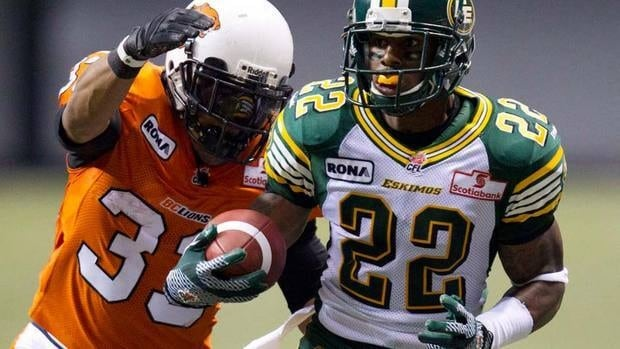 B.C. Lions' Andrew Harris, left, tries to tackle Edmonton Eskimos Joe Burnett during the first half on Friday.