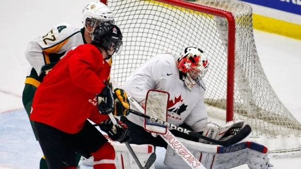 National Junior selection camp goalie Laurent Brossoit, right, blocks a shot during an exhibition game against the University of Alberta Golden Bears in Calgary, Alta., Wednesday, Dec. 12, 2012.