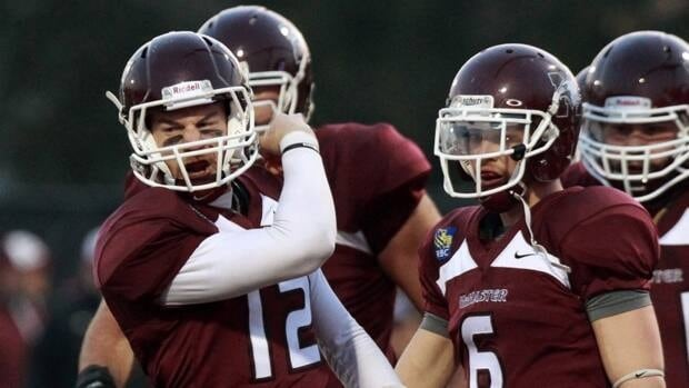 McMaster University Marauders quarterback Kyle Quinlan, left, celebrates with teammate after scoring a touchdown against the University of Calgary Dinos during the Mitchell Bowl in Hamilton, Ontario, on Saturday, Nov. 17, 2012.