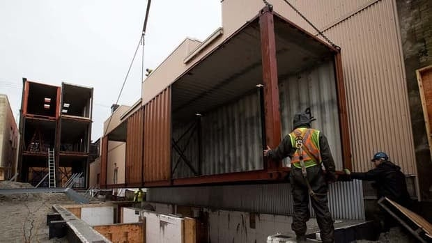 Workers guide a recycled shipping container onto a lot where Canada's first multi-home recycled shipping container housing project is being constructed in Vancouver's Downtown Eastside.