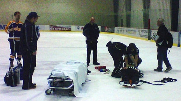 Paramedics tend to a referee after he was pummelled into unconsciousness in June 2011 by a Winnipeg hockey player who was later charged and sentenced to one year in jail.