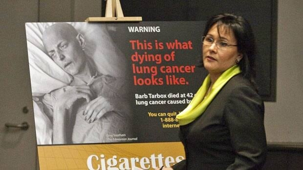 Health Minister Leona Aglukkaq shows an image of lung cancer victim Barb Tarbox.