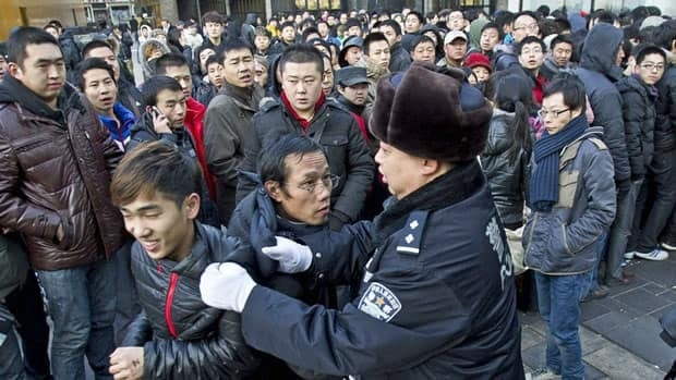 A policeman drags away people who refused to leave an Apple Store in Beijing on Jan. 13, the same day an angry crowd shouted and threw eggs at the store after it failed to open on schedule to sell the new iPhone 4S model.