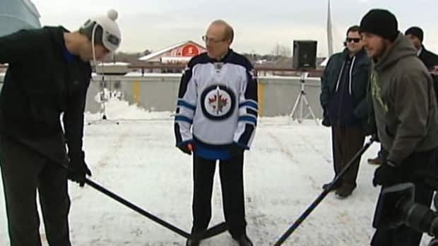 Winnipeg Mayor Sam Katz, centre, drops the hockey ball in a faceoff between team captains Andrew Ladd, left, and Mike Richards at Tuesday's game.
