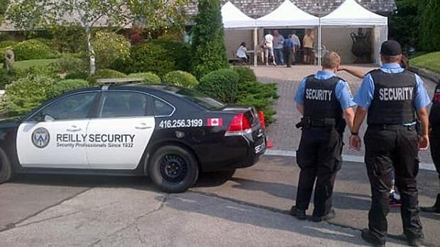 Private security guards size up the situation outside the site of the Ford Fest barbecue ahead of the festivities.