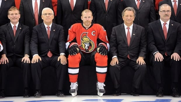 In this photo, Ottawa Senators Daniel Alfredsson is flanked by team president Cyril Leeder, (left to right) GM Bryan Murray, owner Eugene Melnyk and coach Paul MacLean during a team photo at the end of last season. The Sens captain has stayed in Ottawa during the lockout.