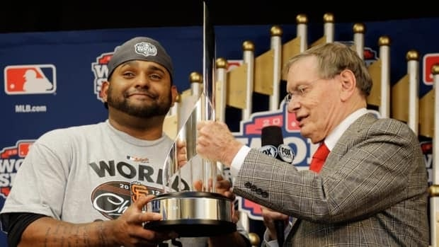 MLB commissioner Bud Selig, right, hands Giants third baseman Pablo Sandoval the World Series MVP trophy.