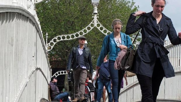 Pedestrians pass a beggar on the Ha'penny Bridge in Dublin, on Sunday. Unemployment in the Republic of Ireland rose to an 18-year high of 14.9 per cent in June. Shawn Pogatchnik/Associated Press
