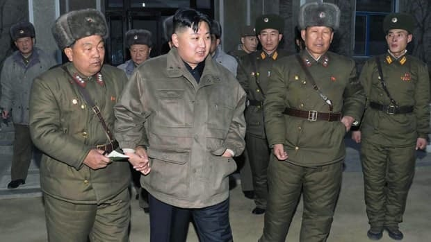North Korean leader Kim Jong-un, centre, raises his arm at an undisclosed location in North Korea, in this undated photo released by the Korean Central News Agency. The U.S. said Wednesday that North Korea has agreed to suspend uranium enrichment.