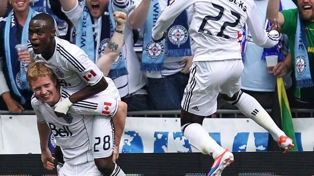 Barry Robson, left, gets mobbed by Vancouver teammate Gerhson Koffie, with Darren Mattocks also celebrating Sunday for the Whitecaps.