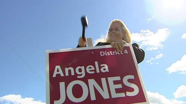 Angela Jones hammers in a sign in District 4 Cole Harbour-Westphal.
