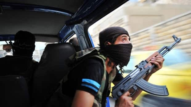 Syrian rebels hunt for snipers after attacking the municipality building in the city centre of Selehattin, near Aleppo, on Monday, during fights between rebels and Syrian troops.