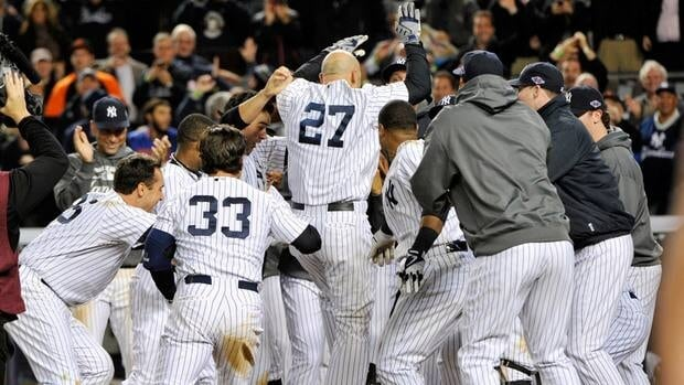 New York Yankees' Raul Ibanez (27) celebrates with teammates as he reaches home plate after hitting the game-winning home run during the 12th inning on Wednesday night.