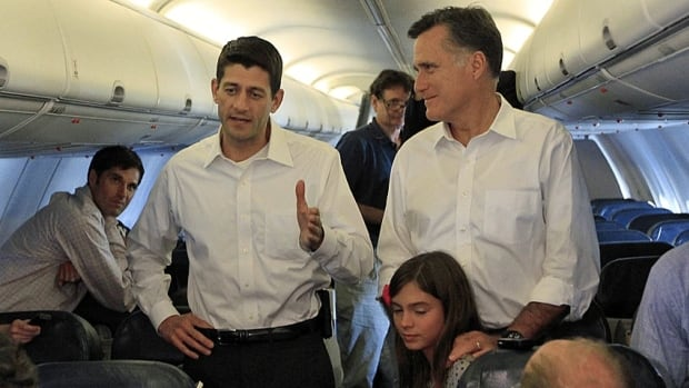 Republican U.S. presidential candidate Mitt Romney, right, stands with his vice president selection Wisconsin congressman Paul Ryan, while speaking to the press aboard a charter flight to Charlotte, N.C.