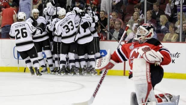 New Jersey Devils' goalie Martin Brodeur gets up from the ice after as the Los Angeles Kings celebrate their winning goal during the overtime period of Game 1 on Wednesday in Newark, N.J.