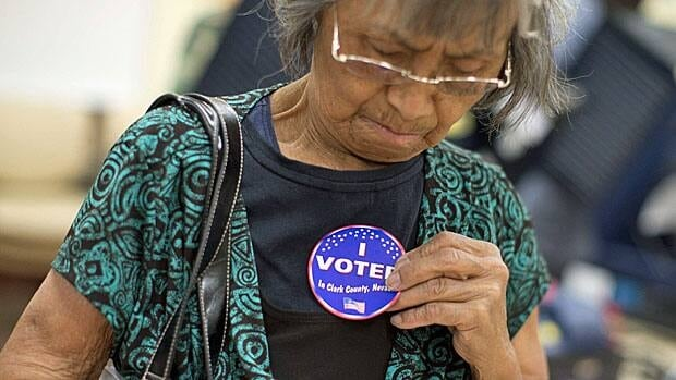 Aida Castillo places a sticker on her blouse indicating that she had voted during the early voting period in Las Vegas, Nev., on Oct. 20.