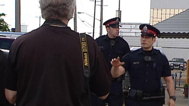Edmonton police pushed reporters back after a plane transporting murder suspect Travis Baumgartner landed at the City Centre Airport Wednesday.