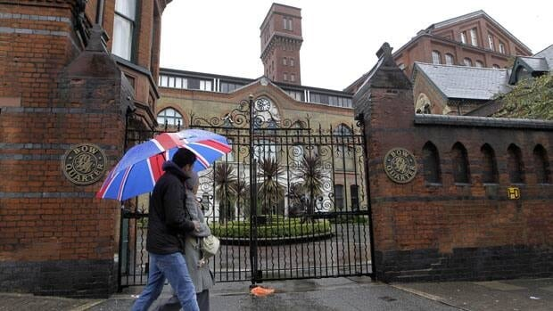 People walk past gated residential flats in Bow, east London, where the Ministry of Defence has warned residents that surface-to-air missiles could be stationed on their rooftops during the London Olympics.