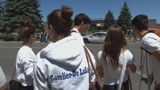 A group of about 50 students dressed in white gathered outside their Montreal high school this afternoon in a show of support for their suspended teacher who showed a graphic video of an alleged murder in his classroom.