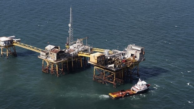 A supply vessel moves near an oil rig damaged by an explosion and fire on Friday in the Gulf of Mexico about 40 kilometres southeast of Grand Isle, La.
