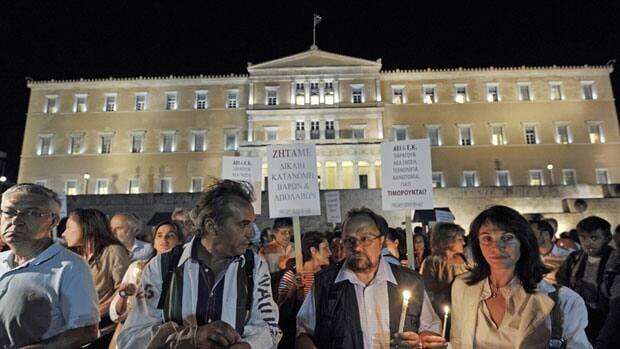 University professors and staff hold candles as they protest in front of the Greek parliament Tuesday against cuts and salaries reductions.