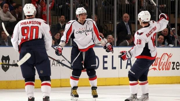 Alex Ovechkin of the Washington Capitals, centre, celebrates with teammates after scoring the winning goal against the New York Rangers.