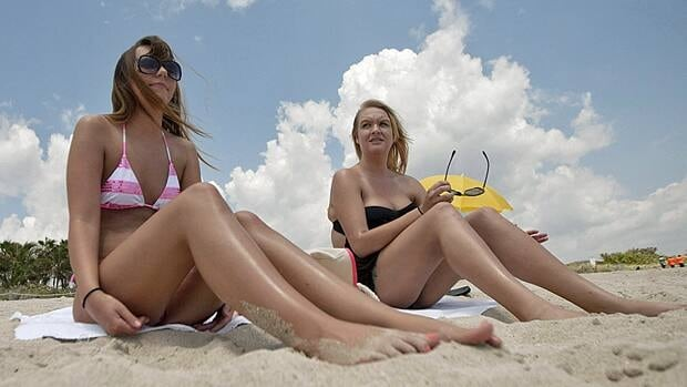 Morgan Weese, 23, left, and Brittany Locke, from Tempe, Ariz. sun bathe in Miami Beach, Fla. during their vacation. Weese said she used to be obsessed with tanning during high school, but now knows the dangers associated with tanning too much.