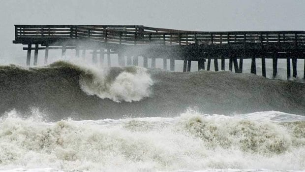 Waves crash on shore from high surf at Virginia Beach, Va., on Monday, presaging storm surges expected along the coast later in the day.