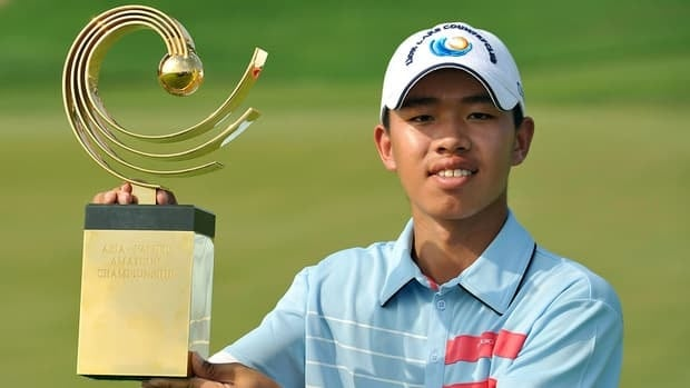 Guan Tianlang of China poses with the winner's trophy at the Asia-Pacific Amateur Championship at Amata Spring Country Club, in Chonburi, Thailand on Sunday.