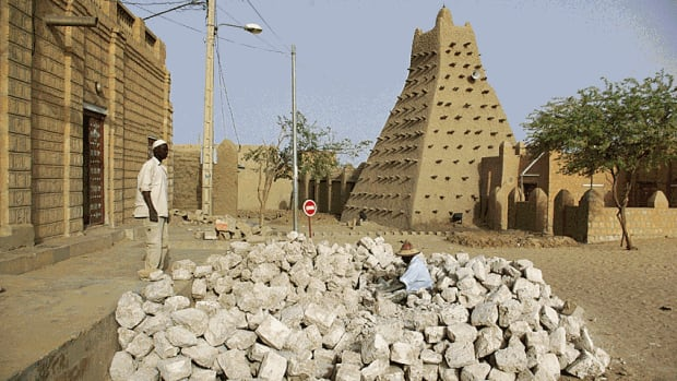 Men work alongside a historic mud mosque in Timbuktu, Mali, in this May 2012 file photo. Locals have vowed to retaliate after Islamist fighters with ties to al-Qaeda desecrated historic shrines.