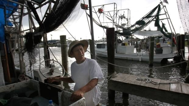 Tuna Pham, a shrimper, talks as he works on his idle boat in Lafitte, La. Two years after the catastrophic BP oil spill, the mood is gloomy on the hard-working shrimp and crab docks of this gritty fishing town in the Barataria estuary, a traditional seafood basket for New Orleans. Fall shrimp and crab catches were down from past years.