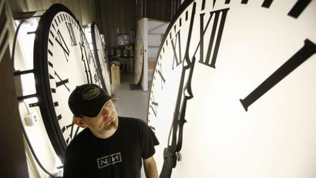 Electric Time Company employee Dan LaMoore tests the lights of three large clocks being constructed at the company's production facility in Medfield, Mass. A quarter of the world's population will move their clocks one hour forward this Sunday to observe daylight saving time.