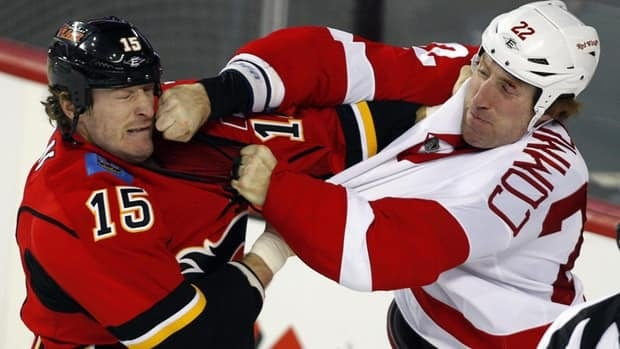 Detroit Red Wings' Mike Commodore, right, lands a punch on Calgary Flames' Tim Jackman as the two fight during first period NHL hockey action in Calgary, Alta., Tuesday, Jan. 31, 2012. Commodore is set to make his debut with the Hamilton Bulldogs on Friday against the Flames' AHL affiliate the Abbotsford Heat.