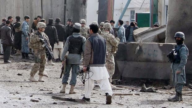 Afghan security forces are seen at the scene of a suicide attack with U.S. soldiers who are part of the NATO-led International Security Forces (ISAF) are seen at the scene of a suicide attack in Kandahar, Afghanistan, which killed one police officer, on Monday. In a separate incident Monday, gunmen in Afghan police uniforms opened fire on NATO troops in southern Afghanistan, killing an Albanian soldier.
