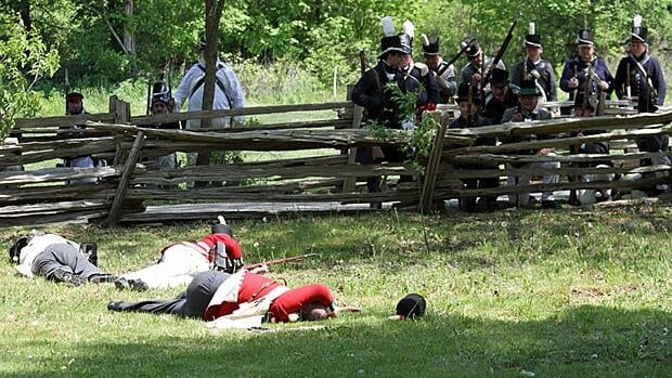 Members of the 89th Regiment lay while the Norfolk Militia looks on during a re-enactment of a skirmish in the War of 1812. The re-enactment happens again today at Westfield Heritage Village.