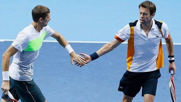 Max Mirnyi, left, and Canada's Daniel Nestor touch hands after they play a return to India's Mahesh Bhupathi and Rohan Bopanna during their doubles match Friday. Nestor failed to reach the semifinals at the year-end event for the first time since 2009.