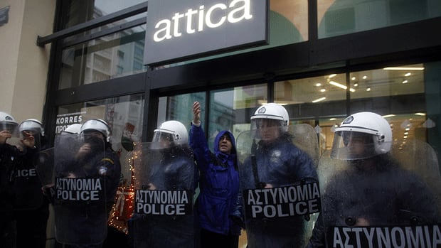 Police guard the entrance of a shopping centre during a protest in Athens.