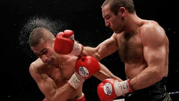 Scott Harrison (R) of Scotland attacks Nedal Hussein of Australia during their WBO Featherweight title fight at the Braehead Arena on November 5, 2005 in Glasgow, Scotland.