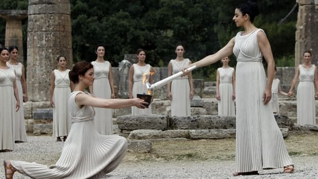 Greek actress Ino Menegaki (R), playing the role of High Priestess, lights the Olympic flame during the torch lighting ceremony of the London 2012 Olympic Games at the site of ancient Olympia in Greece May 10, 2012. REUTERS/John Kolesidis
