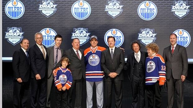 NHL commissioner Gary Bettman, left, poses with Nail Yakupov centre, and Oilers team representatives on stage during the 2012 NHL Entry Draft.