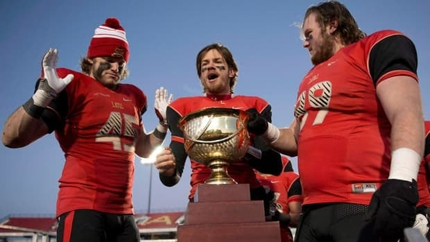 Laval University Rouge et Or quarterback Tristan Grenon, centre, carries the Uteck Bowl trophy after they beat the Acadia Axemen last weekend.