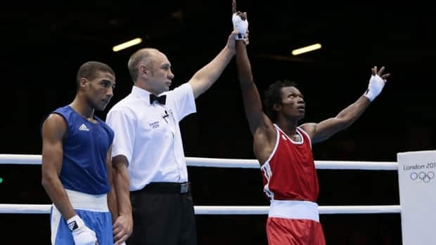Cameroon's Thomas Essomba, right, reacts after defeating Morocco's Abdelali Daraa during their men's light fly 49-kg boxing match at the 2012 Summer Olympics on July 31. Essomba is among seven Cameroon athletes who are missing.