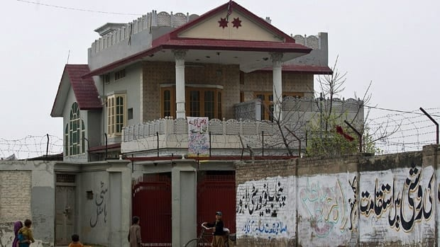 Afghan refugees gather outside the house in Haripur, Pakistan, that Pakistan's intelligence agency believes Osama bin Laden lived in for nearly a year until he moved into the villa where he was eventually killed.