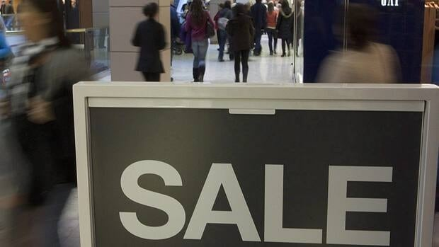 Shoppers walk past a sale sign in a mall in Ottawa in December. The Canadian Federation of Independent Business has asked consumers to use credit cards with lower merchant fees. Pawel Dwulit/Canadian Press