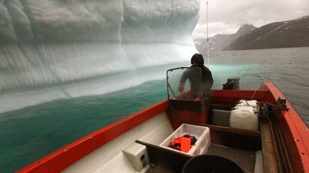 In this July 26, 2011 photo, a Greenlandic Inuit hunter and fisherman steers his boat past a melting iceberg, along a fjord leading away from the edge of the Greenland ice sheet, near Nuuk, Greenland.  The country's delegation to the 2012 Arctic Winter Games said they will bid to be the host of the 2016 games.