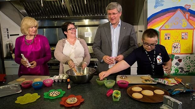 Prime Minister Stephen Harper and his wife Laureen, left, make cookies with 10-year-old brain cancer survivor Baxton Wacholtz, right, and his mother Michelle at Ronald McDonald House in Vancouver on Tuesday.