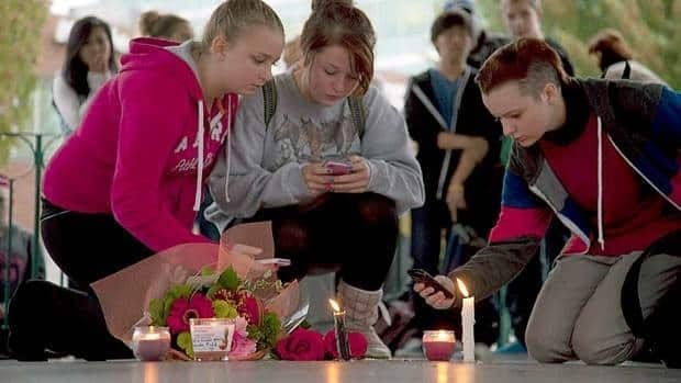 Young people gather at a memorial honouring Amanda Todd in Maple Ridge, B.C., on Monday after the 15-year-old, who was a victim of bullying, took her own life.