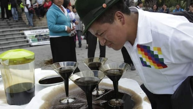 """An indigenous protester in Ecuador looks at """"oil martinis"""" in Quito, during a protest against oil companies. The Ontario Superior Court in Toronto will be the latest venue in a bitter 19-year legal fight between Chevron Corp. and dozens of Ecuadorian Amazon villagers."""