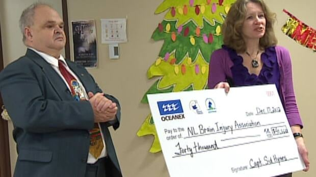 Sid Hynes of Oceanex, with Michelle Ploughman of the N.L. Brain Injury Association, and a giant cheque representing Oceanex's donation.